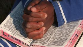 A young African prays with a bible during an outdo