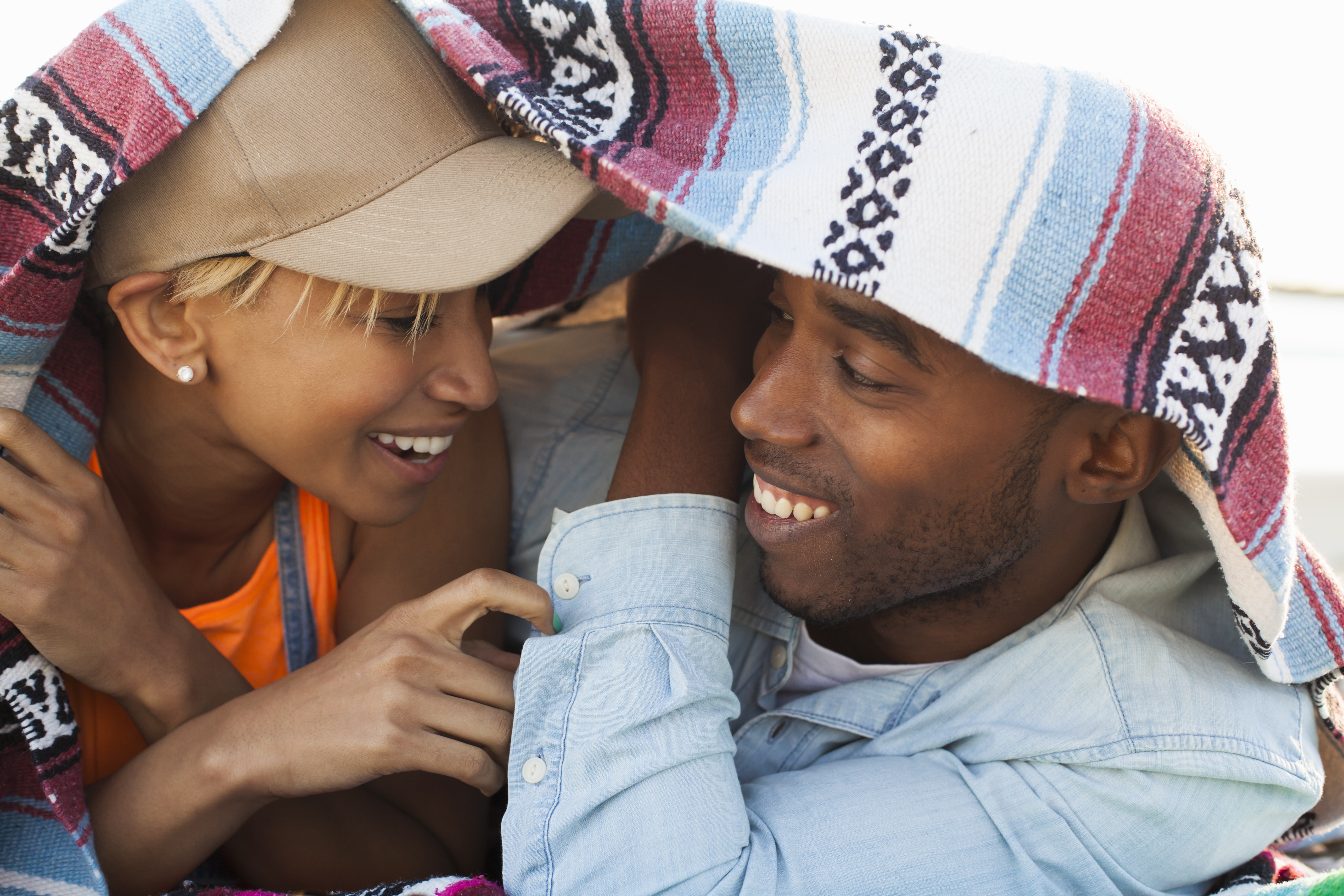Young couple laughing together under picnic blanket
