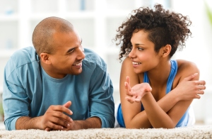 Smiling African American couple lying on carpet and communicating.