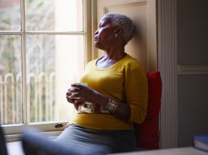 Senior woman looking thoughtfully out window