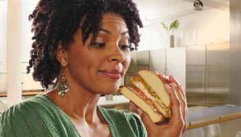 African American woman eating sandwich