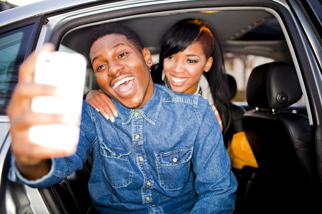 Friends taking photos with a cell phone in a car