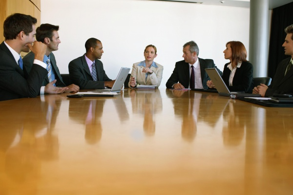 Group of business people at conference table, businesswoman at centre