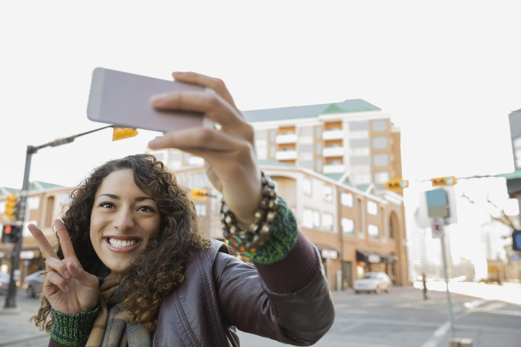 Woman photographing herself with smart phone on city street