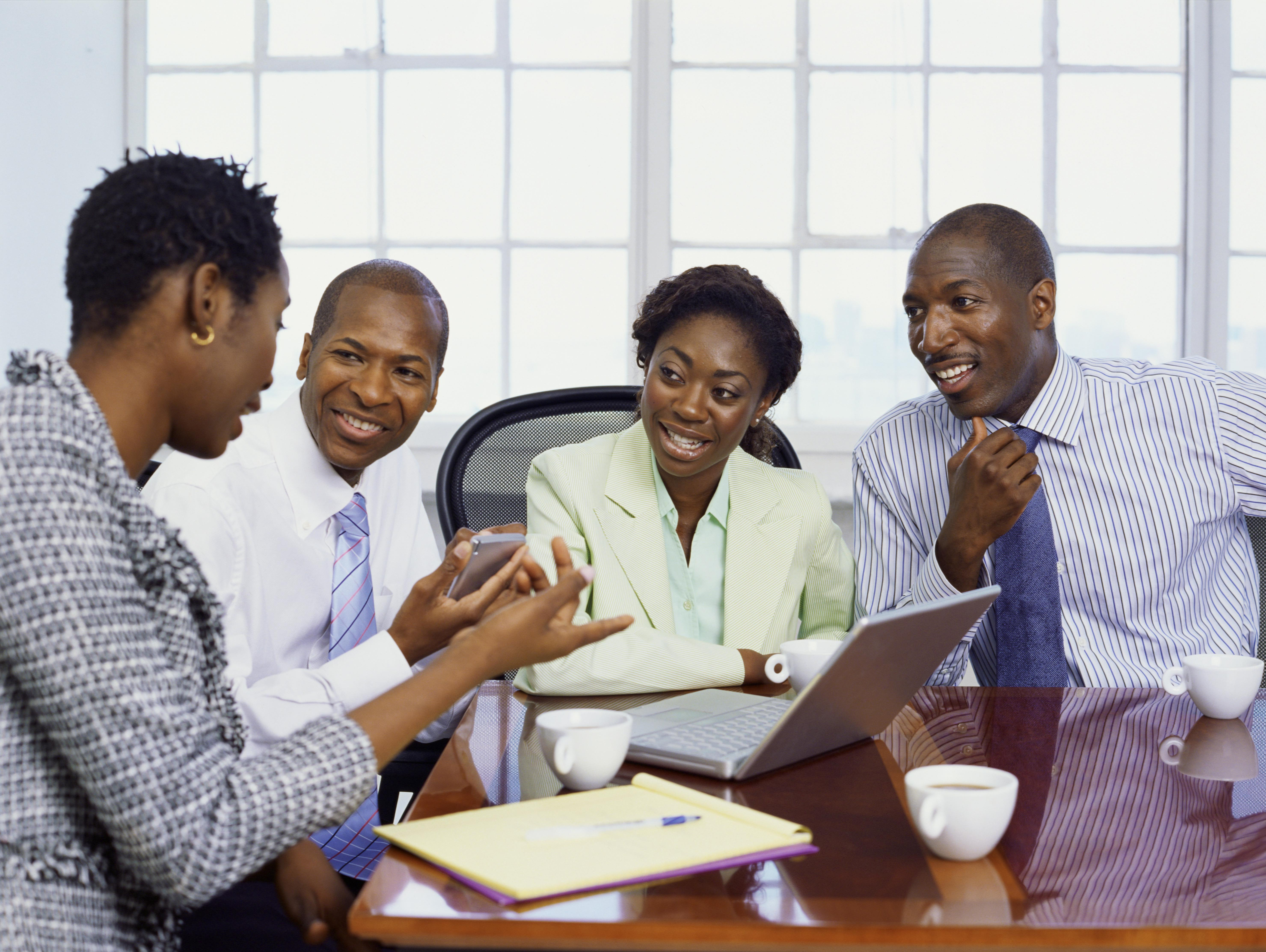 two businessmen and two businesswomen discussing in an office