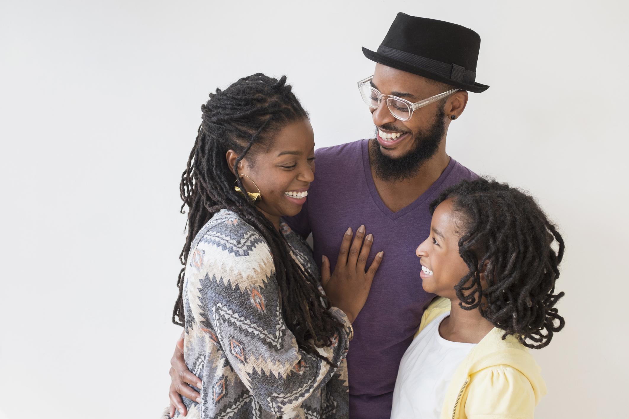 Smiling Black family hugging