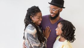 Smiling Black family hugging