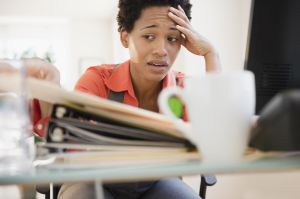 Frustrated African American woman sitting at desk