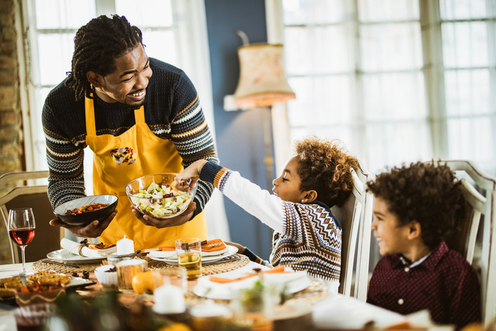 Happy black father serving his kids lunch in dining room.