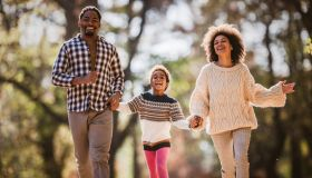 Carefree black family holding hands and running in nature.