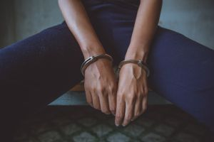 Midsection Of Woman Wearing Handcuffs Sitting In Prison